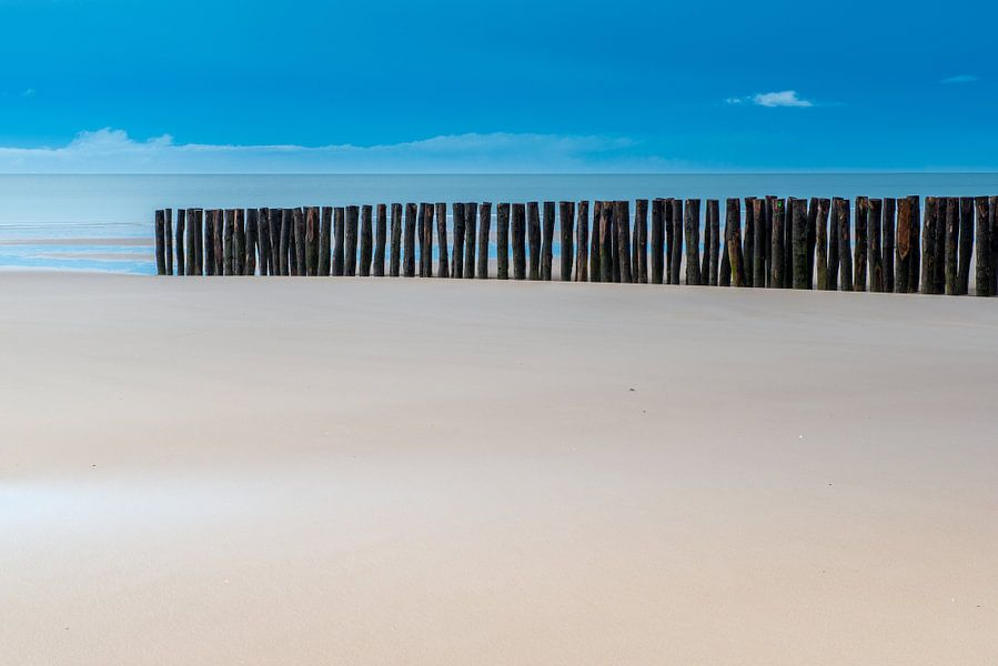 Houten paaltjes op het strand
