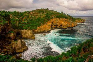 Uitzicht vanaf de heuvelrand op groen rotsstrand en golvende zee. De golven slaan tegen het zandstra
