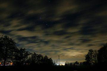 Een nachtfoto van een lucht met wolken en veel sterren. van Julius Koster
