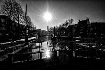 Tegenlicht in Utrecht: De zon, de Domtoren en de Zandbrug vanaf de Weerdsluis in Utrecht in zwartwit van