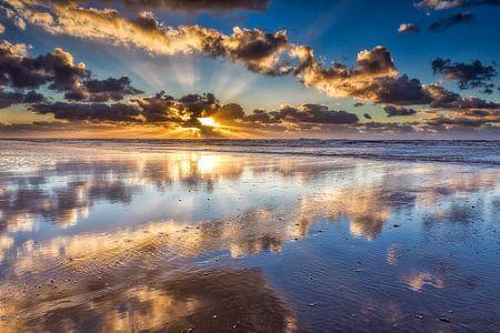 Wolken boven de Noordzee met een zonsondergang