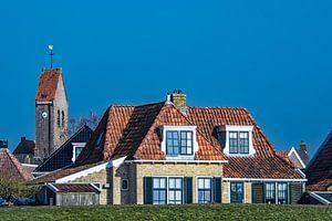 Kerktoren en huizen van het Friese stadje  Makkum achter de IJsselmeerdijk.