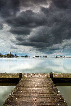 Wolkenlucht met aanlegplaats en zeilboot van Peet Romijn