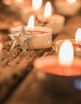 Feestelijk brandende rode advents- en kerstkaarsen met ornamenten in de vorm van een ster van Alex Winter
