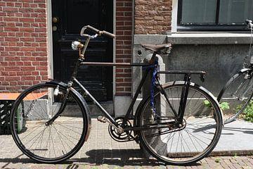 Herenfiets tegen paal aan gracht in Delft van Mariska van Vondelen