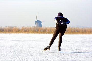 Schaatsen bij de molen op het platteland van Nederland van