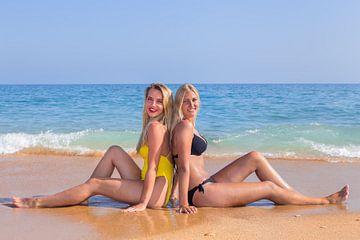 Porträt von zwei Freundinnen die am Meer sitzen von