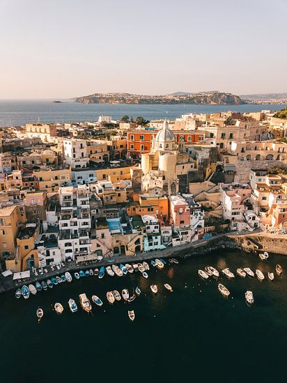 Blick aus der Luft auf den Hafen von Procida mit Ischia im Hintergrund