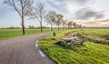 Kromme landweg met houten picknickset in de berm van