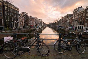 Fietsen met gracht in Amsterdam tijdens zonsondergang