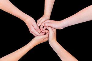 Vijf armen met handen van kinderen verbonden vrijstaand op zwart
