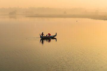 Gondola monte au lever du soleil le long du pont U Mandelay BAIN au Myanmar. Le pont est le plus lon sur