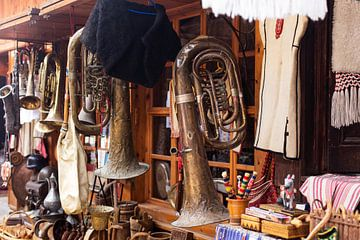 sfeerbeeld van oude trompet hanged voor de ruit van een winkeltje van Giovanni de Deugd
