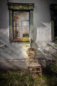 Stuhl vor einem verlassenen Hausfenster