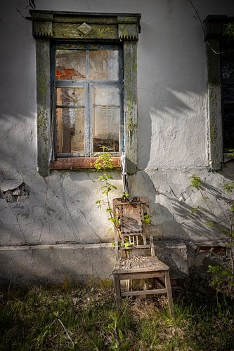 stoel voor een raam van een verlaten huis