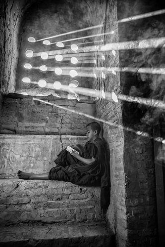 Jonge monnik leest gebedsbundel zittend op een vensterbank van een klooster in Baghan met sterke zon van