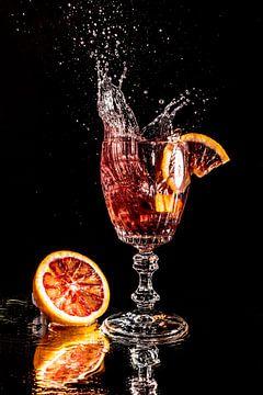 Bloedoranje stuk valt in een glas met water dat gespiegeld wordt op een zwarte achtergrond. van Hans-Jürgen Janda