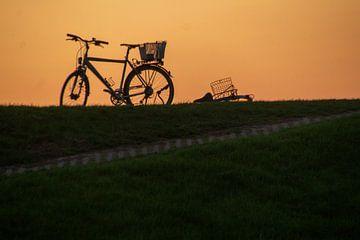 Fahrrad auf Deich gegen untergehende Sonne von wil spijker
