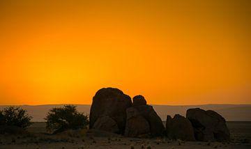 De zon gaat onder achter de rotsen in de Namib woestijn van Rietje Bulthuis
