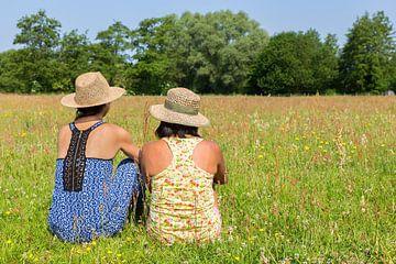 Twee vriendinnen zitten in wei met bloemen van Ben Schonewille