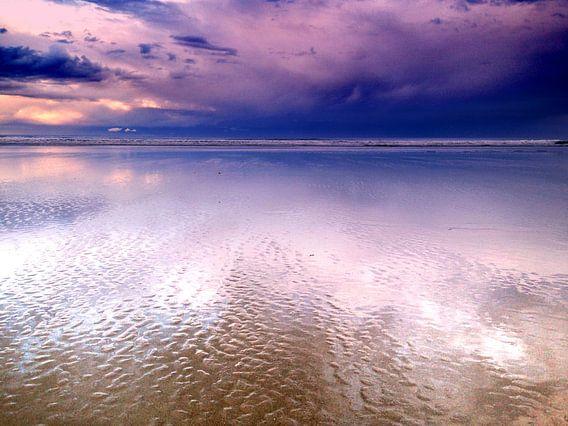 Paarse wolken reflecteren op het strand