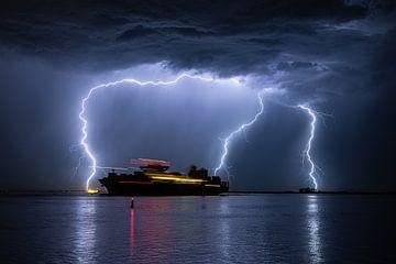 Schip vaart uit tijdens een zware onweersbui van Menno van der Haven