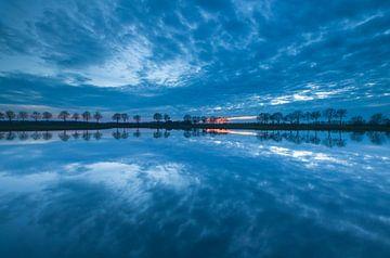 Wolken spiegeling bij zonsondergang van Marcel Kerdijk