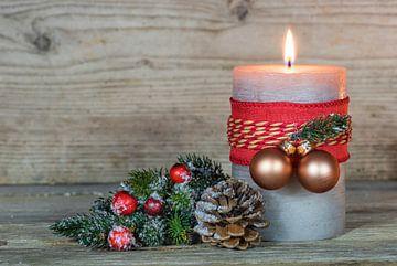 Versierde brandende adventskaarsvlam en gouden kerstballen van Alex Winter