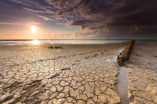 Voetstappen en strekdam in wadden modder bij zonsondergang.