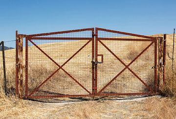 Roestige poort bij een opgedroogd veld