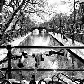 Fietsen in de sneeuw op de Weesbrug  met zicht op de Smeebrug in Utrecht in de winter van De Utrechtse Grachten