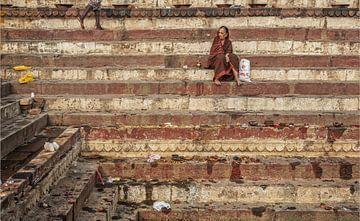 Indiaanse vrouw rust op stappen van een ghat in Varanasi, India. van Tjeerd Kruse
