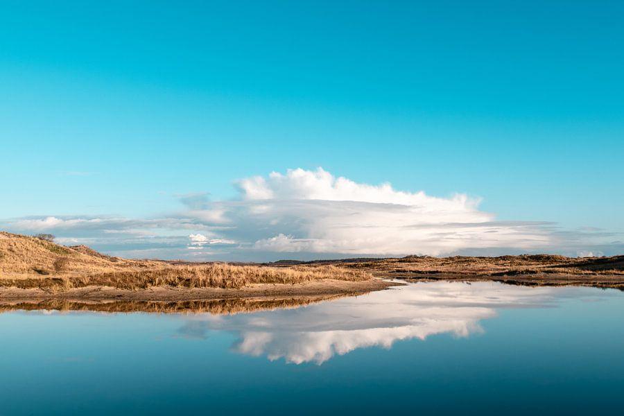 Witte wolk boven de duinen met spiegelbeeld in het water
