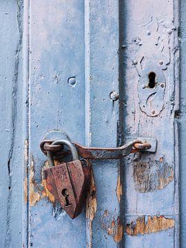 Rostiges Vorhängeschloss an blauer Holztür von Katrin May