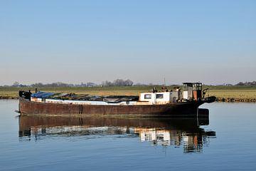 oud verlaten roestig vrachtschip ligt voor anker in het water van R Verhoef