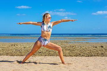 Jonge Nederlandse vrouw in bikini oefent yoga op strand van Hurghada in Egypte van Ben Schonewille