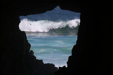 Brechende Welle und fliegender Vogel, durch eine Höhle gesehen von Lau de Winter