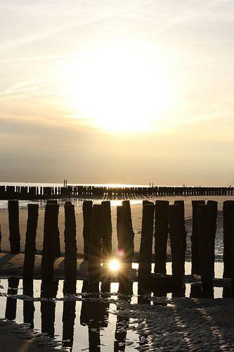 golfbrekers met ondergaande zon op het strand in zeeland