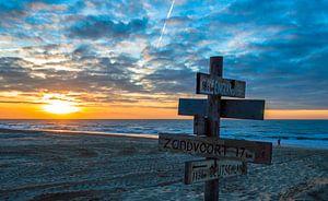 Richtingwijzer met zonsondergang aan de kust