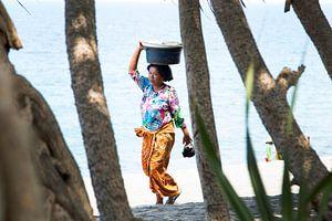 Een Balinese vrouw langs het strand van