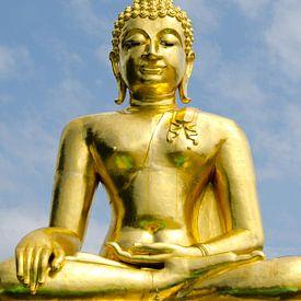 Gouden boeddha tekent af tegen blauwe lucht van Maurice Verschuur