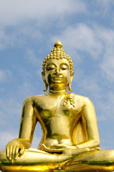Gouden boeddha tekent af tegen blauwe lucht