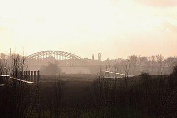 Zicht op Nijmegen met de waalbrug in de winterzon. van Jurjen Jan Snikkenburg