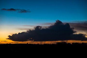 Regenwolk in ochtendlicht van Peter Bouwknegt