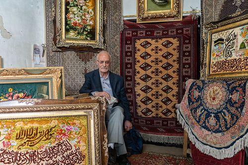 Potrait van de Iraanse man in zijn tapijtwinkel