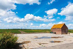Schuur aan weiland onder Hollandse wolkenlucht
