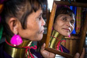 Vrouw behorende tot de long neck tribe in Inle bekijkt zichzelf  van