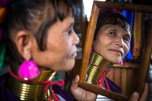 Vrouw behorende tot de long neck tribe in Inle bekijkt zichzelf