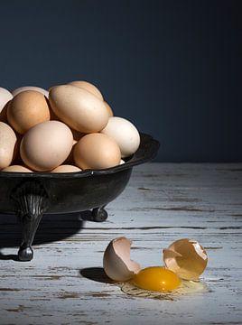 Nature morte avec un plat en étain avec une pile d'œufs et un œuf cassé sur une table blanche à fond sur Leoniek van der Vliet