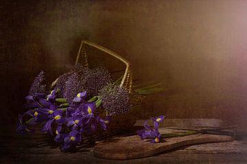 Nature morte avec des iris dans des tons violets dans un panier en osier. sur Saskia Dingemans